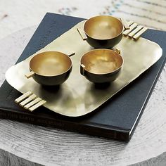 "eastern influence.  Sculptural brass tray by designer Neelima Rao serves a sleek fusion of eastern artistry.  To Rao, the minimal beauty of Japanese kettles, tea ceremonies and sake cups ""have always touched a chord, and I wondered if there was an Indian minimalism I could discover. "" Handcrafted with a subtly rippled surface, raw edge and handcast bar handles, the tray is brushed with layers of patina that flow like an abstract painting.  For decorative use only. neelima rao."