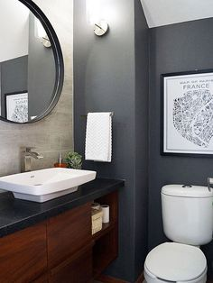 A powder room doesn't have to be done up in white and bright colors to look larger. For her half-bath makeover, blogger Rocio of Casa Haus went with dark gray walls, a wall-to-wall vanity, and an oversize mirror. The white sink, hand towel, and accent wall help keep the tiny bathroom from feeling too heavy. Get more details at Casa Haus./
