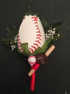 Baseball theme boutonniere featuring a single rose hand cut from the cover of a baseball, a miniature bat, glove and baseball. Adorned with red ribbon stem. Boutonnières can be custom made with requested colors. Message me to create a custom order to combine shipping. Logos and numbers can also be added.