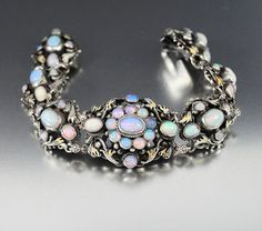 This entrancing antique Victorian Austro Hungarian opal bracelet glows all around with a vibrant palette of pastel colored opals emanating fiery flashes of color. Set in a silver heavy filigree mounti