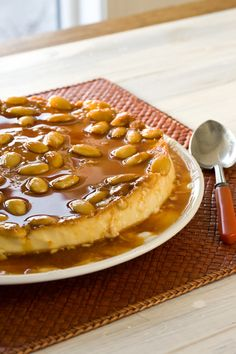 ALMOND ORANGE FLAN 1 1/2 cups sugar, divided 4 cups whole milk 1 teaspoon vanilla extract 1/2 teaspoon almond extract 1/4 teaspoon nutmeg 4 eggs 4 egg yolks -- Finely grated rind of 1 orange 2/3 cup whole blanched almonds, toasted