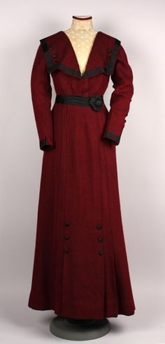 1910-1912 Description - Dress, burgundy and black wool twill with black silk trim and ivory net collar and inset. High stand style collar and inset of ivory net.