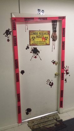 Zombie Research Facility front door decoration. Blood static cling stickers from Walmart, sign and zombie hand from Spirit Halloween