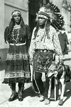 Indian couple will ride horses across continent Date October 1930 Summary:   View of Little Chief White Eagle, a Yaqui Native American wearing leggings, kilt with an embroidered swastika, shirt and a headdress and Princess Rainbow Sistesso, a Sioux, in a fringed buckskin dress, walking on a sidewalk with a dog wearing moccasins, Los Angeles, California. http://cdm15330.contentdm.oclc.org/cdm/singleitem/collection/p15330coll22/id/23638/rec/1