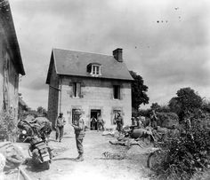 Troops of the 3rd Armored Division relax in the courtyard of a French farm after the fighting to capture Coutances on the 29th of July.