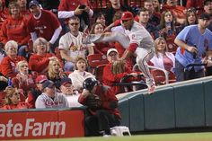 Philadelphia Phillies Ben Revere hurdles an usher after making a catch on a ball off the bat of St. Louis Cardinals Jon Jay in the seventh inning at Busch Stadium in St. Louis on April 28, 2015. St. Louis won the game 11-5. Photo by Bill Greenblatt/UPI