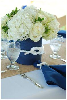 Decoração para casamento na praia feito com arranjos de hortênsias e rosas brancas em vasos azuis com detalhe em corda. #casamento #praia #noivas #noiva #decoração #azuis #flores #tema #marinho #mar