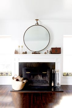 Fireplace with styled with a round mirror and gold candle sticks