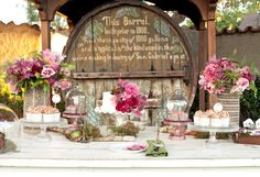 Great idea to set-up dessert table (or any table) in front of a focal piece such as the wine barrel (don't always have to think about creating a piece to serve as the backdrop you know?). Loving the different heights created by the stands, vases, etc. And of course the gorgeous array of florals/foliage used really gives the table life