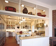 "Architect Robert A.M. Stern and interior designer Mariette Himes Gomez collaborated on a Southampton house. Above: The kitchen. ""Equipment and wares are meant to be seen and to provide the ambience of a cook's kitchen,"" says Stern. Sub-Zero refrigerator. Thermador ovens; Viking cooktop. Chicago faucets and Waterworks sink in foreground. KitchenAid microwave. (March 2005)"
