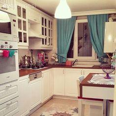 Country stil mutfak mavi bir perde ve renkli mutfak aksesuarlarıyla tamamlanmış..
