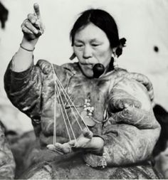 """Pikatnaaq's wife, Helen Konek's mother playing """"ajagaq"""".  This game represents a tent. The person could include stories or little songs about the tent. These games were also important in building associations and personal relationships as well as passing along oral histories and traditions. String games were like picture shows and also developed important skills. As the person demonstrated the game, you had to guess what it would become. The games built memory, observation and creativity…"""