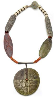 Ethnic Disk Neckpiece made of carved polymer, sterling silver, antique coral, waxed linen.