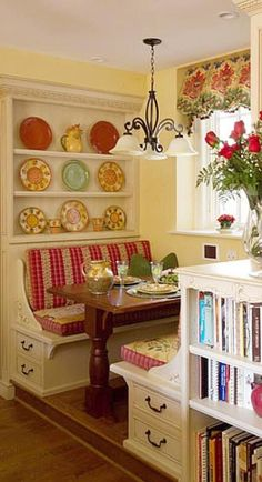 A very versatile breakfast nook with comfortable striped, upholstered benches, plate racks, and even cookbooks nearby.