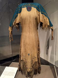 """Lakota woman's dress, 1855, from the Central Plains. Made of native-tanned leather, glass beads, brass bells. Loaned by the Smithsonian's National Museum of the American Indian Installation view of """"The Plains Indians: Artists of Earth and Sky"""" March 9 - May 10, 2015 Metropolitan Museum of Art New York, New York"""