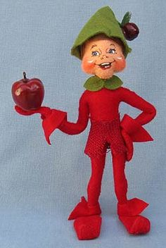 Annalee Doll Description: Open eyes, mouth expression may vary, brown hair, green hat with red apple at tip, green collar, red body with red burlap skirt, holds red apple. Companion is 351513.