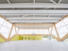 Clear glazing forms the lower facade of this gymnasium to offer views of the sports field, while the southern side is opaque to avoid too much glare.