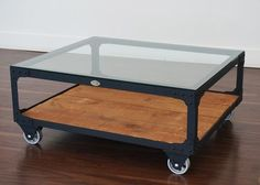 """Industrial Coffee Table - Factory Cart Coffee Table - Featuring a flat black steel finish, an oak color wood shelf stain and a 3/8 inch clear glass table top. Fastened with rivets and accent corner brackets, mounted on 5 inch casters and features a decorative vintage style brass boilerplate on front. 40"""" L x 34"""" W x 17"""" H, 135 lbs.  Duty Free"""