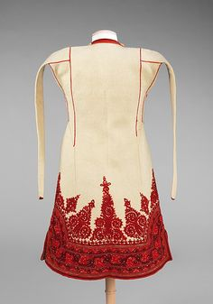 Coat Date: 1890–1910 Culture: Albanian Medium: wool, metal, silk Dimensions: Length at CB: 39 in. The flared and fitted shaped of this sleeveless coat is achieved through piecing. The ornate couching includes carefully placed light and dark elements that create an overall shaded effect. The vestigial sleeves may have developed from a folk tradition of draping a coat over the shoulders.