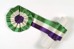 Suffragettes' ribbon in the shape of a rosette. This ribbon in green white and purple was worn in the Suffragette movement and probably worn as a belt, with the rosette on the clasp. Date: 1905 - 1914