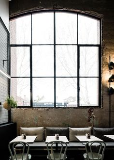 Patch Cafe in Melbourne. The large arched steel window provides abundant light to the narrow space. The built-in seating is upholstered in heavy-duty fabric to offset the soft hues of the space.