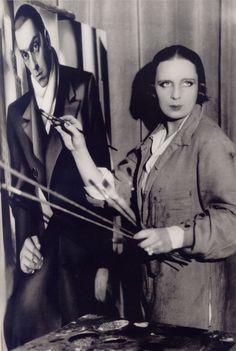 Tamara de Lempicka in front of the portrait of her husband Tadeusz (1928) - by Thérèse Bonney