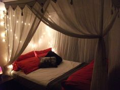 sheer tied back drapings around the bed with string lights behind the headboard.