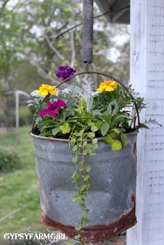 I absolutely LOVE rusty buckets.  Fill one with a smaller plastic container, find some old springs to hang it, and a few clumples of pretty flowers and you got yourself a work of art.......D.