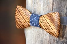 Exotic Wooden Bow Tie - Zebrawood. This wooden bow tie is handcrafted from Zebrawood, an exotic hardwood native to West Africa. The wood grows in straight, interlocking stripes which then are cut on the bias (diagonal) to form the pattern seen here. It is finished with mineral oil and beeswax (both edible) which help prevent the wood from drying out while still keeping its natural feel. Straps come in random colors and are not visible once the bow ties are put on. Adjustable sliders on…