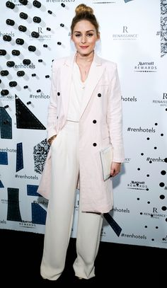 OLIVIA PALERMO in a light pink trench-style jacket over wide-leg white pants and a blouse with an Adornmonde string choker