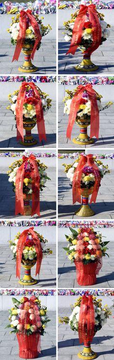 위대한 김일성동지와 김정일동지의 동상에 외국의 단체, 인사들과 연고자가족들이 꽃바구니를 보내여왔다-《조선의 오늘》