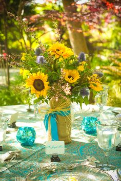 Sunflower bouquet wrapped with bright blue ribbon, adorable way to reuse the bridesmaid bouquets as centerpieces. #wedding #centerpieces