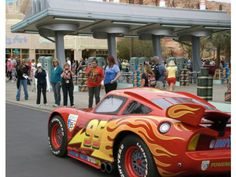 Visitors to Cars Land watch Lightning McQueen, a streetmosphere car based on the character from the Disney/Pixar animated movie Cars, drives down Route 66 in Cars Land's Radiator Springs. The gas station is actually Flo's V8 Cafe, a restaurant.