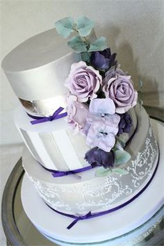 "Sarah (2) : Three tier wedding cake - sugar roses, hydrangeas, lisianthus and eucalyptus on silver lustered and pure silver leaf cake with hand piped white detail design and ""tie the knot"" wording.  Finished with fine satin purple ribbon, tied in a knot.  Two moist rich fruit cake tiers, marzipanned and iced and one vanilla bean paste sponge tier with whipped raspberry, Chambord and vanilla bean paste buttercream, also marzipanned and iced."