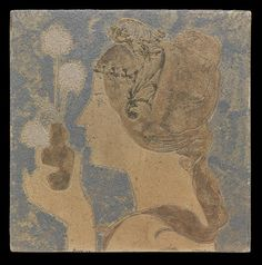This ceramic tile was made by the ceramist Greber Charles (1853-1935). It represents a young lady's profil, holding a vase with three dandelion. Charles was inspired by the Art Nouveau, since this tile was designed during the apogee of this style, around 1900.