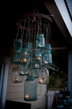"""Rusty Wheel & Old Blue Mason Jars...re-purposed into a rustic """"chandelier"""" with battery operated tea lights."""