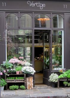 The dark grey tones of this space perfectly set off the floral arrangements out the front. The high-arch windows also add to the dramatic effect. Vertige | Paris