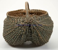 FINE VIRGINIA PAINTED RIB-TYPE WOVEN-SPLINT BASKET, white oak, kidney form with converging ribs, double-wrapped rim, and low arched handle. Exceptional original worn dry blue-green painted surface. Fourth quarter 19th century