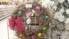 Burlap easter wreath with colorful eggs and bright pink bow
