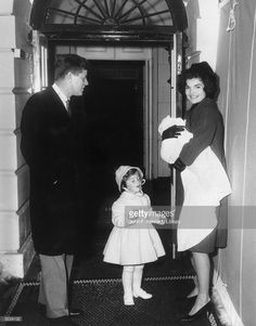 President John F. Kennedy (1917 - 1963) smiles as he stands with his wife, First Lady Jacqueline Bouvier Kennedy (1929 - 1994), and their daughter, Caroline, in front of a doorway at the White House, Washington, D.C. Jacqueline Kennedy holds John Kennedy Jr. (1960 - 1999) in her arms.
