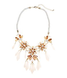 Statement collar necklace with twisted cord, rhinestones, and metal pendants. | H&M Accessories