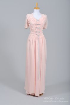 Designed in the 40's, this lovely bias-cut vintage wedding gown is done in a pink silk chiffon over a pink crepe lining. The bodice features a squared sweetheart neckline, high back and ruched capped