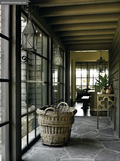 love this hallway with stone floor, steel windows..... also, loving the lanterns and basket