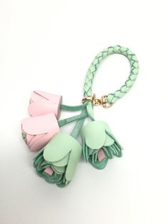 This tassel is one of our best creations. It measures almost 5 inches ( 13-14cm ) All pieces are made from real leather features 2 pink and 2 Aqua green roses and a braided handle Adjustable length This piece is only shipped via priority mail