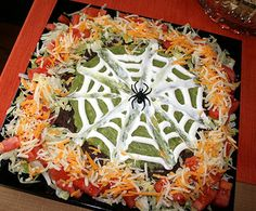 Layered Mexican dip with sour cream web and olive spider