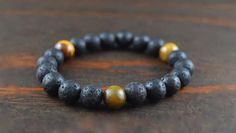 • Mens Beaded Lava Bracelet. Mens Yoga Bracelet. Lava Stone Bracelet. Tiger Eye Bracelet. Beaded Bracelet. Lotus & Lava Bracelet. Yoga Gift • • Lava stone provides the strength, fire, & power contained within it. It is a stone of courage which allows one the opportunity for stability throughout changes in their lives. • Tiger's eye is used to focus the mind, which allows clearer thinking & insight. It helps you face and overcome difficult challenges. Materials: 10mm Lava Stone Bea...