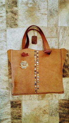 A Gorgeous Womans Personalized Leather Tote Bag,Brown Leather Hand Bag  Spacious, sophisticated and chic, this gorgeous camel tote leather embellished with studs, is a must-have leather bag. With the monogram you can make this beautiful designer bag into your own one of a kind bag.  It is roomy, functional and versatile, with two handles to carry over your shoulder.  You can use it everywhere every day and for any occasion, and it will add charm, elegance and sophistication to your…
