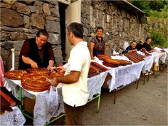 """Women lined up outside of Geghard Monastery in August selling freshly-made sweet bread, known as gata, and """"sour lavash"""", a type of fruit roll-up made from fresh Armenian fruit."""