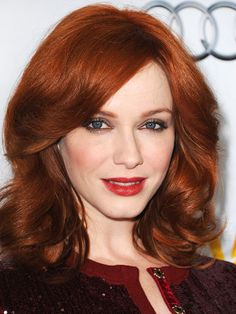Christina Hendricks feathered, thick waves with red lipstick and a taupe smoky eye