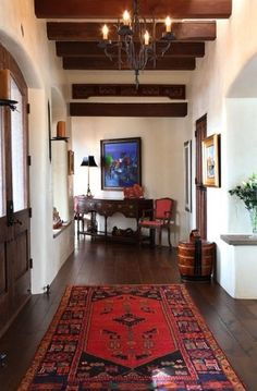 Dark floors with oriental rugs & white walls. Spanish Colonial Home Interior - Hall - Tewes Interior Design